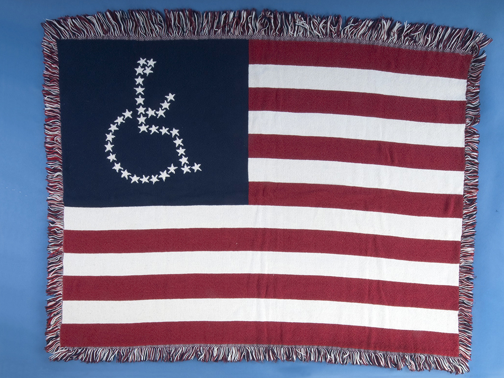 Universal Access Flag Lap Blanket, made by American Disabled for Attendant Programs Today. Gift of Carol Jones to National Museum of American History, Smithsonian Institution.